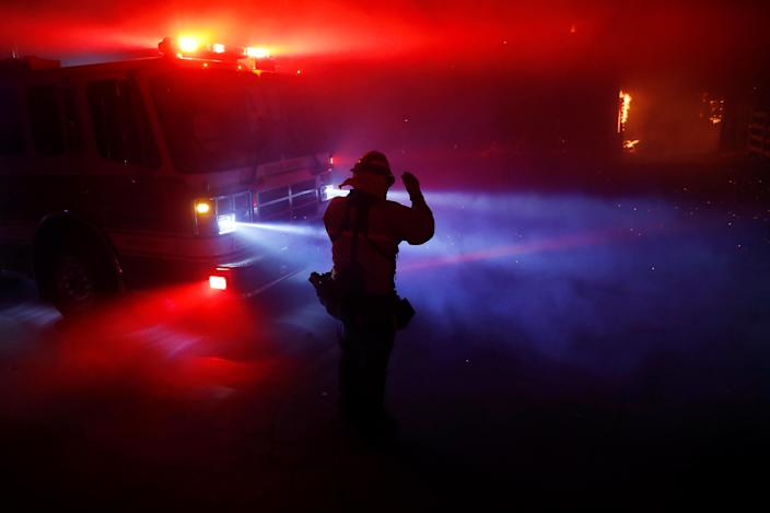 A firefighter walks through thick smoke illuminated by fire engine lights and embers during the wind-driven Kincade Fire in Windsor, California, Oct. 27, 2019. (Photo: Stephen Lam/Reuters)