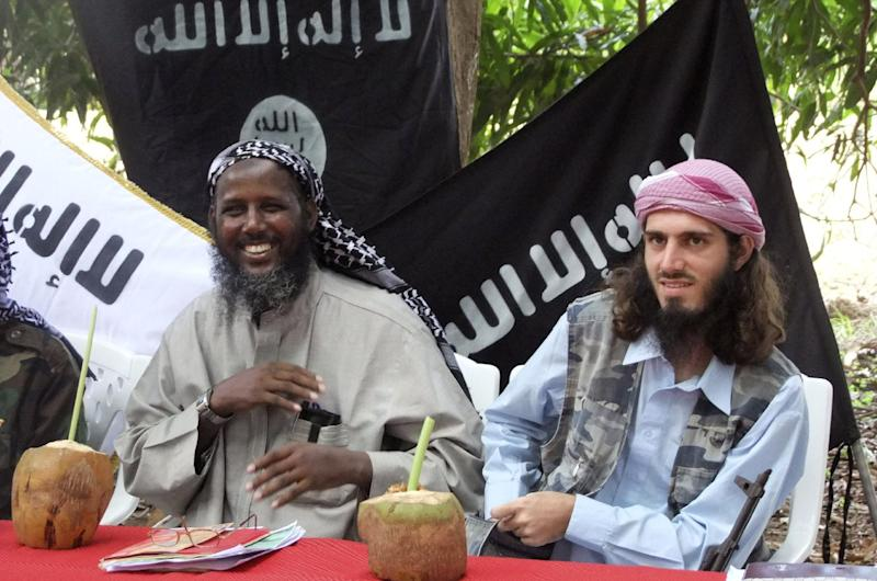 """FILE - In this Wednesday, May 11, 2011 file photo, American-born Omar Hammami, also known as Abu Mansur al-Amriki, right, and deputy leader of al-Shabab Sheik Mukhtar Abu Mansur Robow, left, sit under a banner which reads """"Allah is Great"""" during a news conference by the militant group at a farm in southern Mogadishu's Afgoye district in Somalia. Hammami - whom the FBI named as one of its most wanted terrorists in November - has engaged in a public fight with al-Shabab over nearly the last year and may soon find himself the one pursued by insurgents. (AP Photo/Farah Abdi Warsameh, File)"""