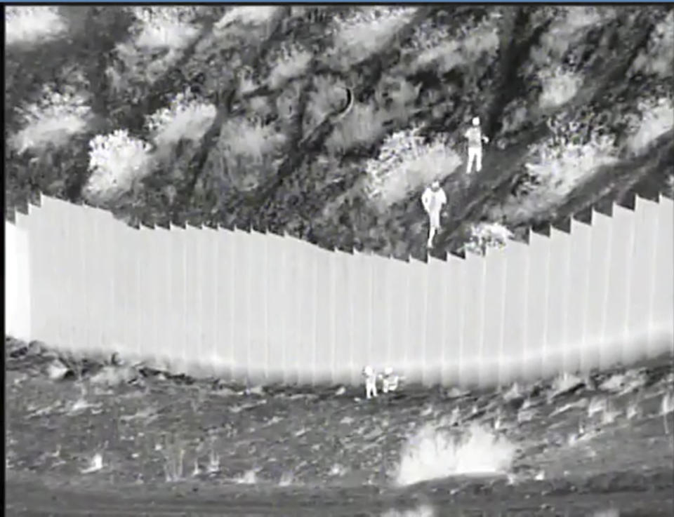 This Tuesday, March 30, 2021, photo taken from night video provided by the U.S. Customs and Border Protection shows smugglers, upper right after dropping two children from the top of border barrier in Santa Teresa, N.M. From a video released Wednesday by federal authorities showing two Ecuadoran children being abandoned by smugglers after they were dropped over a 14-foot-high barrier along the U.S.-Mexico border. Authorities said Santa Teresa border agents were able to find the 3- and 5-year-old sisters after being directed by the camera operator to the remote location in New Mexico, just west of El Paso, Texas. The girls were alert but were taken to a hospital to be checked out and cleared. (U.S. Customs and Border Protection via AP)