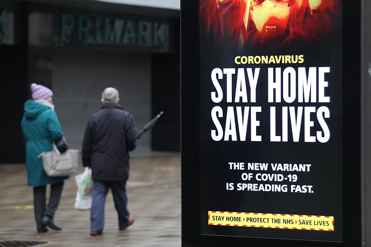 People walk past a 'Stay Home Save Lives' government sign on Commercial road in Portsmouth during England's third national lockdown to curb the spread of coronavirus. (Photo by Andrew Matthews/PA Images via Getty Images)