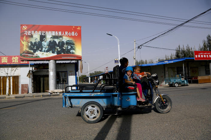FILE - In this Sept. 20, 2018, file photo, an Uighur woman shuttles school children on an electric scooter as they ride past a propaganda poster showing China's President Xi Jinping joining hands with a group of Uighur elders in Hotan, in western China's Xinjiang region. The prominent British human rights lawyer Geoffrey Nice is convening an independent tribunal in London with public hearings in 2021, to look into the Chinese government's alleged rights abuses against the Uighur Muslim minority in the far western province of Xinjiang.(AP Photo/Andy Wong, File)