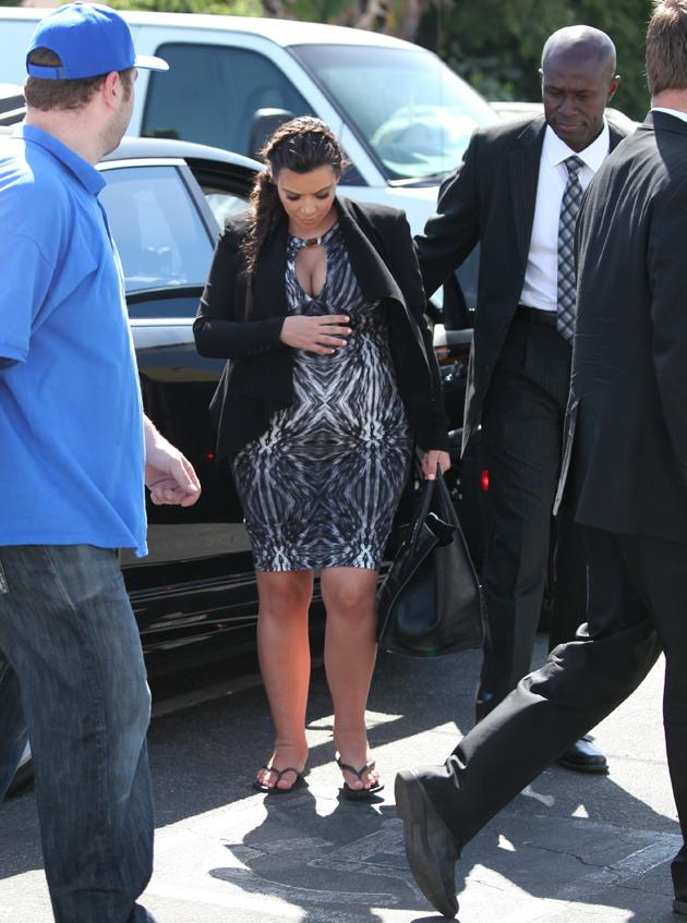 Kim Kardashian shows off her baby bump in a tight patterned dress teamed with a black blazer, and flip flops for her seriously swollen feet. Copyright [Splash]