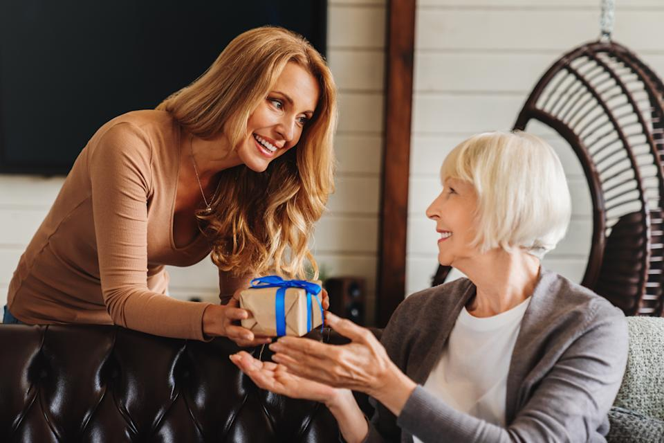 Middle aged female child making present greeting her happy senior mother indoor