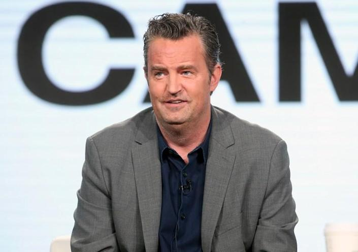 Matthew Perry in a gray suit and dark shirt in 2017