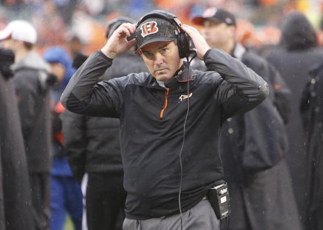 FILE - IN this Jan. 5, 2014 file photo, Cincinnati Bengals defensive coordinator Mike Zimmer adjusts his head set in the second half of an NFL wild-card playoff football game against the San Diego Chargers, in Cincinnati. The Minnesota Vikings have chosen Zimmer as their new head coach, according to multiple media reports. Zimmer will replace Leslie Frazier, who was fired after the team finished 5-10-1 this season. (AP Photo/David Kohl, File)