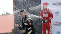 Josef Newgarden gets sprayed with champagne by Marcus Ericsson in victory lane after winning the IndyCar race at Mid-Ohio Sports Car Course in Lexington, Ohio, Sunday, July 4, 2021. (AP Photo/Tom E. Puskar)