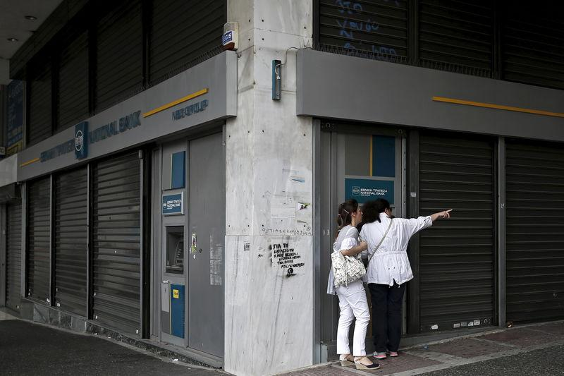 A woman using an ATM machine gestures to her friend outside a closed National Bank branch in Athens