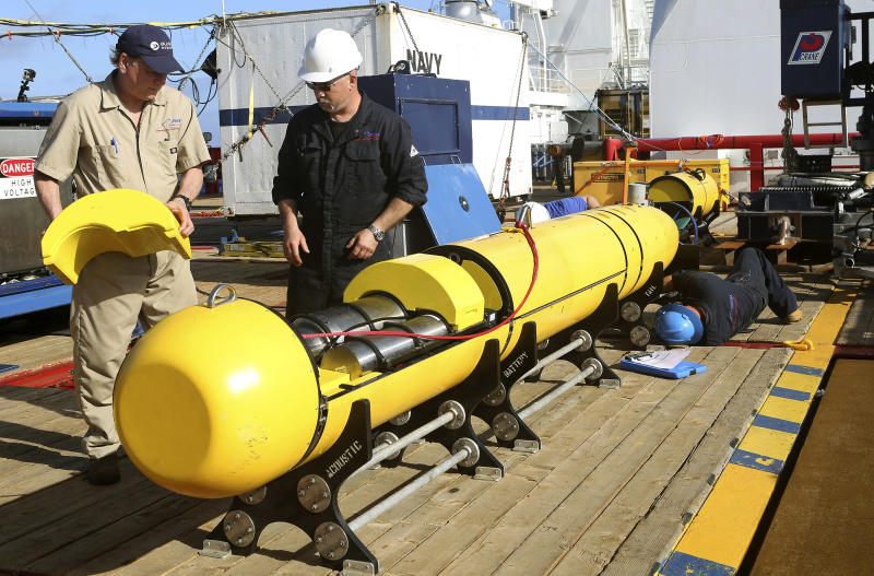 In this Monday, April 14, 2014, photo provided by the Australian Defense Force Phoenix International's Chris Minor, right, and Curt Newport inspect an autonomous underwater vehicle before it is deployed from ADV Ocean Shield in the search of the missing Malaysia Airlines Flight 370 in the southern Indian Ocean. The search area for the missing Malaysian jet has proved too deep for the robotic submarine which was hauled back to the surface of the Indian Ocean less than half way through its first seabed hunt for wreckage and the all-important black boxes, authorities said on Tuesday. (AP Photo/Australian Defense Force, Lt. Kelli Lunt) EDITORIAL USE ONLY