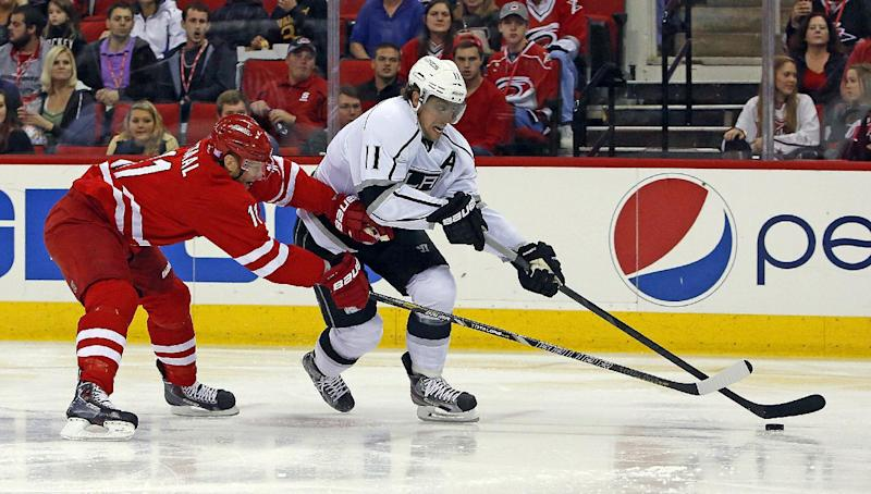 Los Angeles Kings' Anze Kopitar, right, of Slovenia, drives past Carolina Hurricanes' Jordan Staal during the first period of an NHL hockey game, Friday, Oct. 11, 2013, in Raleigh, N.C. (AP Photo/Karl B DeBlaker)