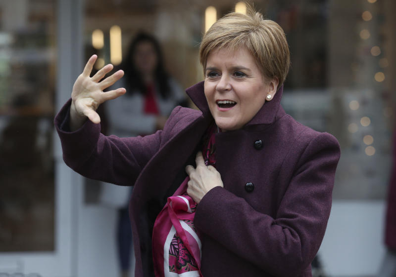Scottish National Party leader Nicola Sturgeon, right, waves to SNP supporters during a visit to Dalkeith, Scotland, while on the General Election campaign trail, Wednesday Dec. 4, 2019. Britain's Brexit is one of the main issues for political parties and for voters, as the UK goes to the polls in a General Election on Dec. 12. (Andrew Milligan/PA via AP)