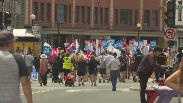 Students marched down Water Street in St. John's on Saturday to oppose Memorial University's announced tuition hike. (Emma Grunwald/CBC - image credit)