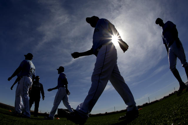Seattle Mariners pitcher Yusei Kikuchi, center, from Japan, walks to a practice field during spring training baseball practice, Tuesday, Feb. 12, 2019, in Peoria, Ariz. (AP Photo/Charlie Riedel)