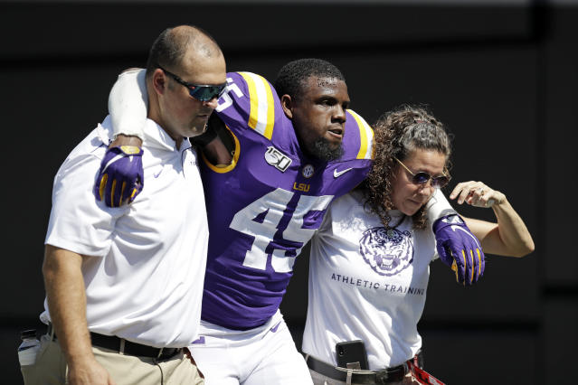 LSU linebacker Michael Divinity Jr. (45) is helped off the field after being injured in the first half of an NCAA college football game against Vanderbilt Saturday, Sept. 21, 2019, in Nashville, Tenn. (AP Photo/Mark Humphrey)