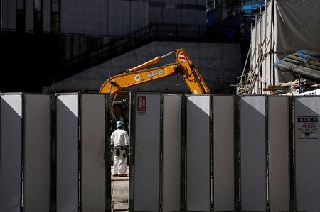 FILE PHOTO: A worker is pictured next to heavy machinery at a construction site in Tokyo's business district, Japan, January 16, 2017.    REUTERS/Toru Hanai/File Photo