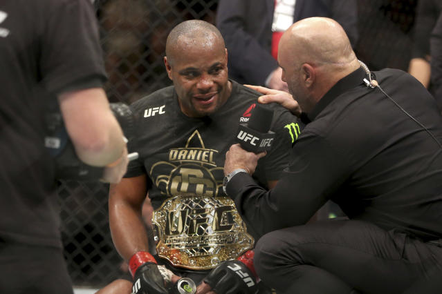 Daniel Cormier is interviewed by Joe Rogan after a win over Volkan Oezdemir after a light-heavyweight championship mixed martial arts bout at UFC 220, Saturday, January 20, 2018, in Boston. Cormier retained the title via 2nd round TKO. (AP)