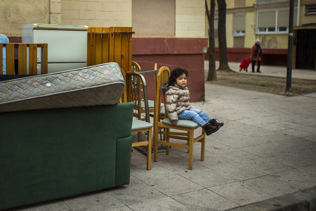 <p>Diana Sofia Meliton, 2, sits outside with her family's belongings after their eviction by police in Madrid, Feb. 11, 2015. (AP Photo/Andres Kudacki) </p>
