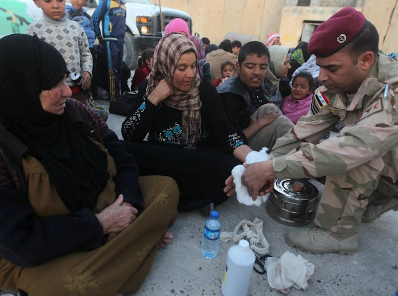 A displaced Iraqi Sunni woman who fled from a village near the northern Iraqi city of Tikrit due to fighting between IS group militants and government forces receives medical treatment at an army camp in Samarra on March 8, 2015 (AFP Photo/Ahmad Al-Rubaye)