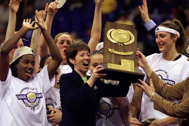 FILE - In this April 1, 2001, file photo, Notre Dame coach Muffet McGraw, center, holds up the National Championship trophy after Notre Dame defeated Purdue 68-66 for the 2001 Women's Final Four Championship in St. Louis. At left is Imani Dunbar and Ruth Riley is at right. McGraw abruptly retired Wednesday, April 22, 2020, stepping down from Notre Dame after a Hall of Fame coaching career that includes two national championships in 33 seasons. (AP Photo/Michael Conroy, File)
