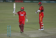 Islamabad United' Paul Stirling, left, raises bat to celebrate after scoring fifty while teammate Alex Hales watches duirng a Pakistan Super League T20 cricket match between Islamabad United and Quetta Gladiators at the National Stadium, in Karachi, Pakistan, Tuesday, March 2, 2021. (AP Photo/Fareed Khan)