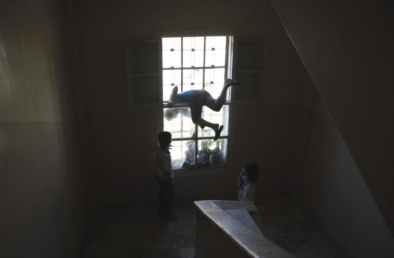 A Syrian boy plays with others in the school where they took refuge from the fighting, in the town of Kafr Hamra, some ten kilometers .(six miles) north of the center of Aleppo city, Syria, Tuesday, Aug. 7, 2012. (AP Photo/ Khalil Hamra)