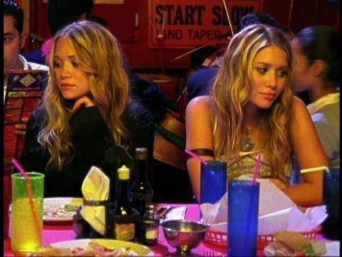 """Mary-Kate and Ashley Olsen in """"The Challenge,"""" sitting at a table"""