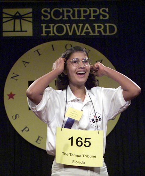 "FILE – In this June 3, 1999 file photo Nupur Lala, 14, from Tampa, Fla. reacts upon winning the 72nd annual National Spelling Bee in Washington after correctly spelling ""logorrhea."" Like all bee winners, she's since had to deal with the perks, drawbacks and stereotypes that come with the title — all magnified because she won the same year the competition was featured in an Oscar-nominated documentary.Today, she's 28 and finishing up a master's degree in cancer biology with plans to enroll in the University of Texas Medical School in Houston, having changed course from a career plan that had her researching memory and the brain for three years at MIT. (AP Photo/Ron Edmonds, File)"