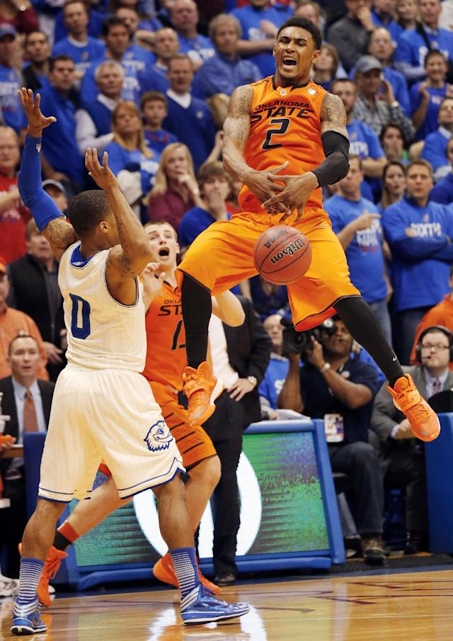 Oklahoma State guard Le'Bryan Nash (2), covered by Kansas guard Frank Mason (0), mishandles the ball while trying for a last second shot during the second half of an NCAA college basketball game at Allen Fieldhouse in Lawrence, Kan., Saturday, Jan. 18, 2014. Kansas defeated Oklahoma State 80-78. (AP Photo/Orlin Wagner)