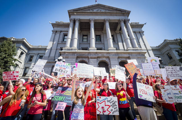 <p>Thousands of teachers and supporters hold up a variety of different signs and end their rally in front of the capital building after marching from Civic Center Park in Denver, Colo., on Friday, April 27, 2018. (Photo: Dougal Brownlie/The Gazette via AP) </p>