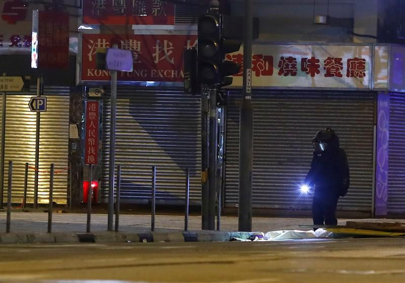 A police technician looks for explosive devices after a protest in the Mong Kok area in Hong Kong