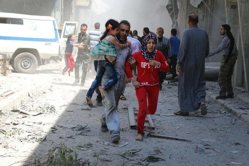 A Syrian family runs for cover amid the rubble of destroyed buildings following a reported air strike in Aleppo, on April 29, 2016