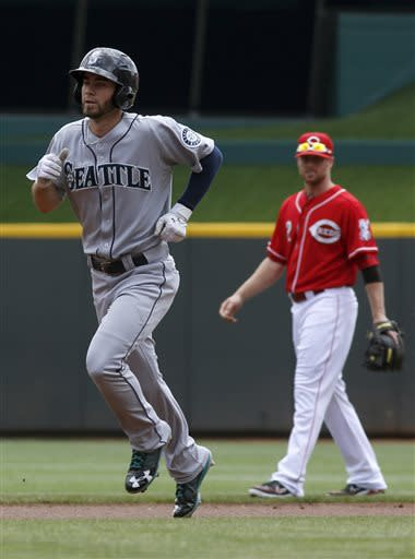 Seattle Mariners' Nick Franklin, left, rounds the bases past Cincinnati Reds shortstop Zack Cozart, right, after hitting a solo home run of Reds pitcher Bronson Arroyo in the first inning during a baseball game on Sunday, July 7, 2013, in Cincinnati. (AP Photo/David Kohl)