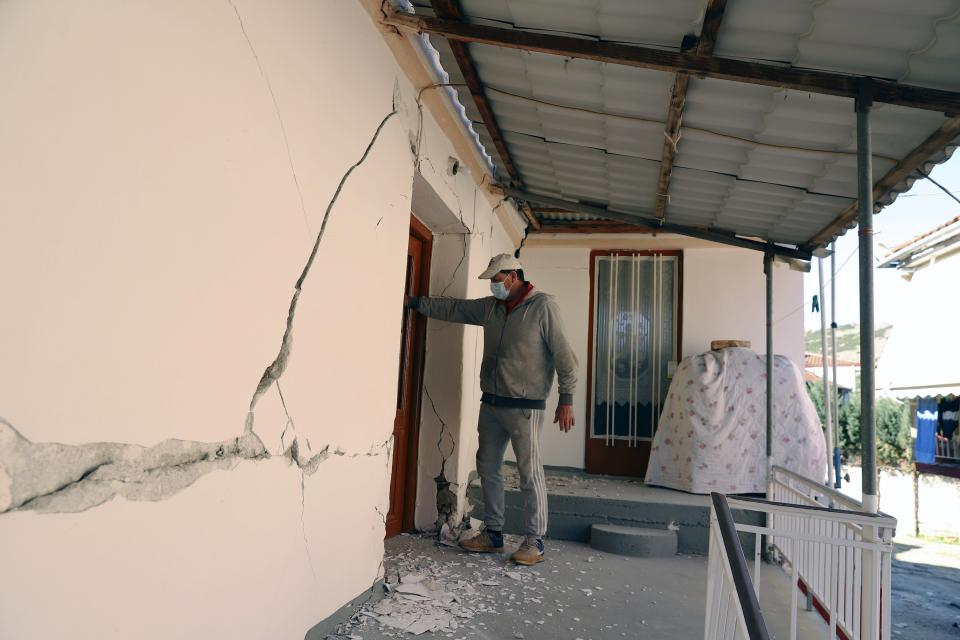 A man checks a house after an earthquake in Damasi village, central Greece, Wednesday, March 3, 2021. An earthquake with a preliminary magnitude of up to 6.3 struck central Greece on Wednesday and was felt as far away as the capitals of neighboring Albania, North Macedonia, Kosovo and Montenegro. (AP Photo/Vaggelis Kousioras)