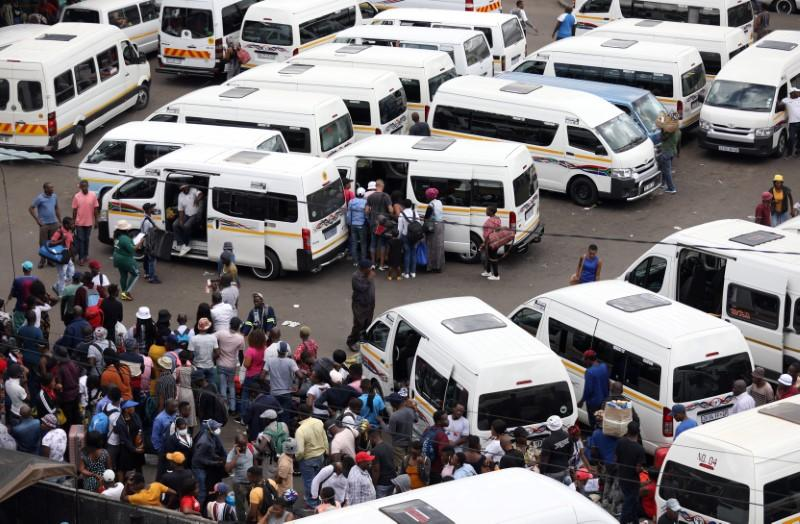 Passengers are seen at at taxi rank as residents of a number of African cities where the coronavirus is spreading are heading to the countryside to try to escape from the disease, in Johannesburg