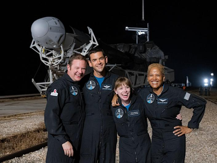 inspiration4 crew poses in front of falcon 9 rocket that's laying sideways on runway at night