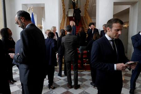 FILE PHOTO: French President Emmanuel Macron and Prime Minister Edouard Philippe use their smartphones after a family photo after the first cabinet meeting at the Elysee Palace in Paris