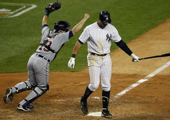 Alex Rodriguez retreats to the dugout after striking out to end Game 5 of the ALDS as Detroit catcher Alex Avila celebrates the Tigers' series victory