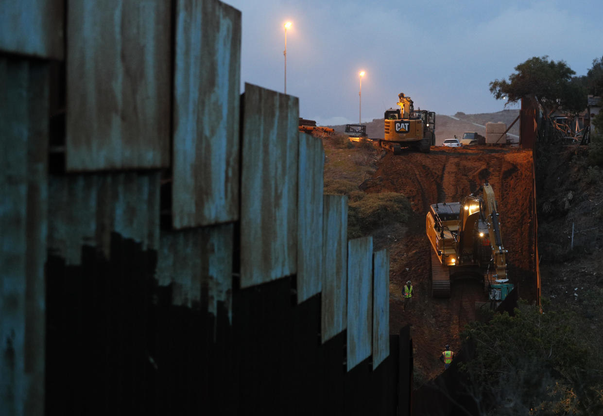 Contractors work to reinforce a section of the U.S. border wall between San Diego and Tijuana, where scores of Central American migrants have crossed illegally in recent weeks. (Photo: Rebecca Blackwell/AP)