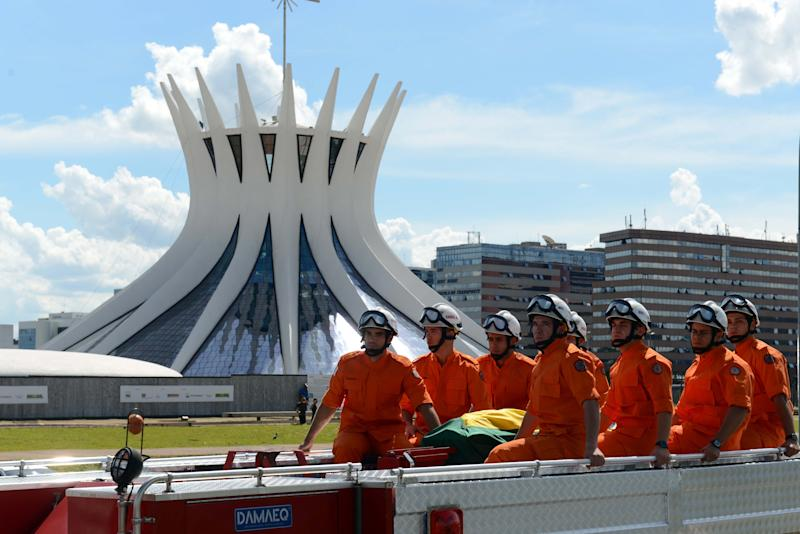 A fire truck escorting the coffin containing the remains of Brazilian architect Oscar Niemeyer drives past the Metropolitan Cathedral, on its way to the Planalto presidential palace, in Brasilia, Brazil, Thursday, Dec. 6, 2012. Niemeyer, 104, the groundbreaking architect who designed Brazil's futuristic capital, including the Metropolitan Cathedral, and much of the United Nations complex, died Wednesday night in Rio de Janeiro, the seaside city where he was born and where his remains will be buried after he is honored with a service in Brasilia at the presidential palace he designed.