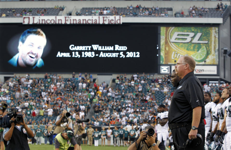 Philadelphia Eagles coach Andy Reid, right, stands on the field as sign shows a photo of his son Garrett Reid, who died Sunday, before an NFL preseason football game against the Pittsburgh Steelers on Thursday, Aug. 9, 2012, in Philadelphia. (AP Photo/Mel Evans)