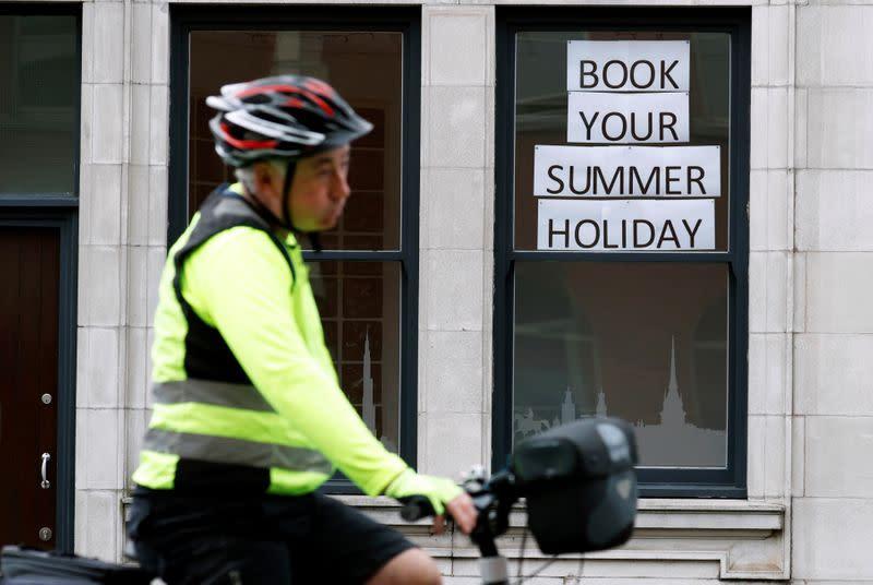 Man rides a bicycle past a travel agents store, in Manchester
