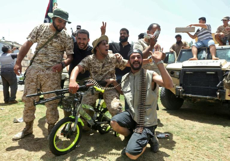 Fighters loyal to Libya's UN-recognised Government of National Accord pose for a picture with a children's bicycle as they celebrate the capture of the town of Tarhuna, about 65 kilometres southeast of the capital Tripoli