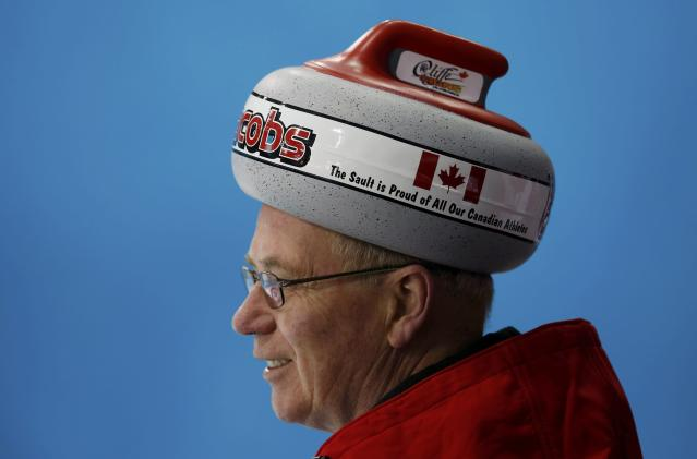 A fan of Canada wearing a hat in the shape of a stone looks on during their men's curling round robin game against Germany at the 2014 Sochi Olympics in the Ice Cube Curling Center in Sochi February 10, 2014. REUTERS/Mark Blinch (RUSSIA - Tags: OLYMPICS SPORT CURLING TPX IMAGES OF THE DAY)
