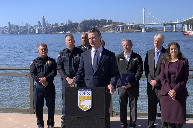 Gov. Gavin Newsom, center, speaks at a news conference with other officials to announce the state's new earthquake early alert system on the 30th anniversary of the Loma Prieta earthquake, Thursday, Oct. 17. 2019, in Oakland, Calif. Earthquake early warning alerts will become publicly available throughout California for the first time this week, potentially giving people time to protect themselves from harm, the Governor's Office of Emergency Services said Wednesday. (AP Photo/Terry Chea)