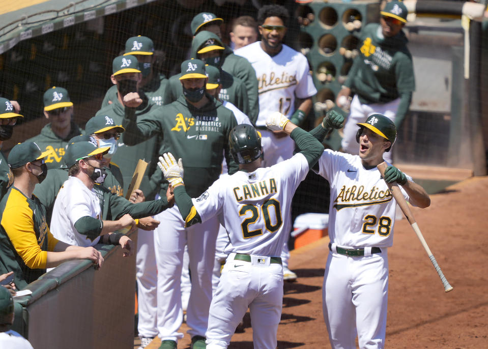 Oakland Athletics' Mark Canha (20) celebrates with Matt Olson (28) after hitting a solo home run against the Detroit Tigers during the second inning of a baseball game on Saturday, April 17, 2021, in Oakland, Calif. (AP Photo/Tony Avelar)