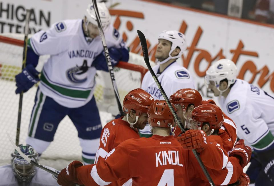 Detroit Red Wings defenseman Jakub Kindl (4), center Stephen Weiss, left, wing Tomas Tatar, lower right, congratulate center Pavel Datsyuk (13), of Russia, on his goal during the second period of an NHL hockey game against the Vancouver Canucks in Detroit, Sunday, Nov. 30, 2014. (AP Photo/Carlos Osorio)