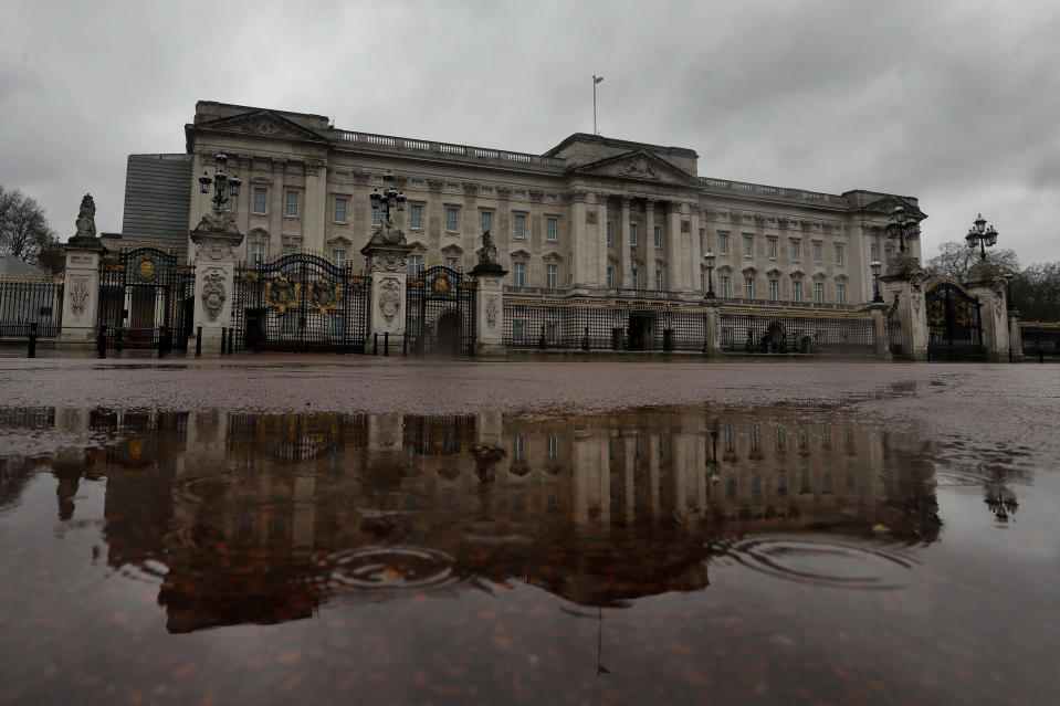 Buckingham Palace is reflected in a rain puddle in London, Wednesday, March 10, 2021. In countries with historic ties to Great Britain, allegations by Prince Harry and Meghan about racism within the royal family have raised questions about whether those nations want to be closely connected to Britain anymore after the couple's interview with Oprah Winfrey. (AP Photo/Kirsty Wigglesworth)