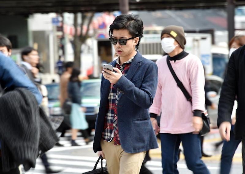 A pedestrian using his smartphone on a street in Tokyo, November 3, 2014. Growing ranks of cellphone addicts are turning cities into increasingly hazardous hotspots (AFP Photo/Yoshikazu Tsuno)
