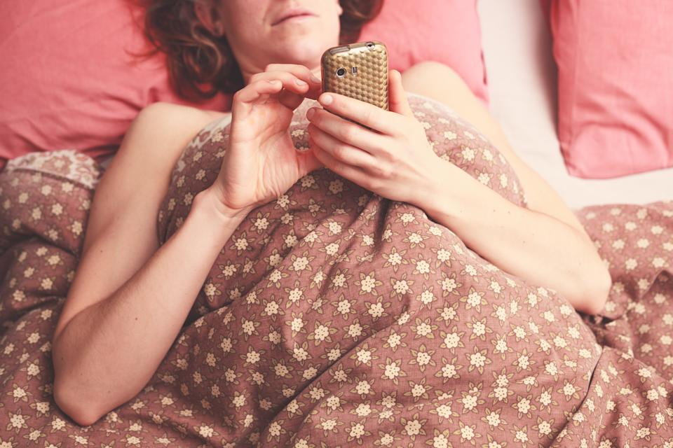 Young woman is lying in bed and sending a text on her phone
