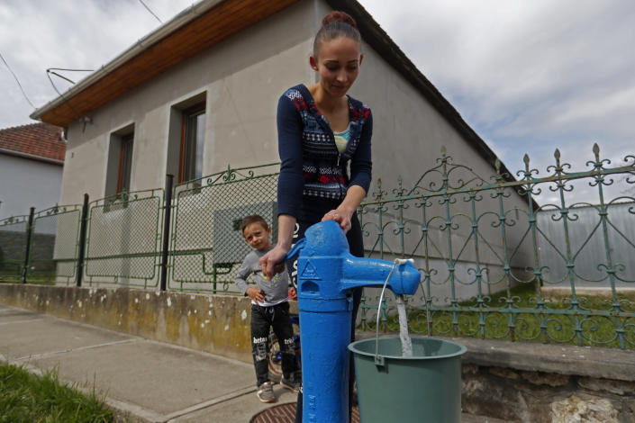 Karmen Bastyur, a 22 year old Hungarian Roma woman, fills a bucket with drinking water from a public water pump in Bodvaszilas, Hungary, Monday, April 12,2021. Many students from Hungary's Roma minority do not have access to computers or the internet and are struggling to keep up with online education during the pandemic. Surveys show that less than half of Roma families in Hungary have cable and mobile internet and 13% have no internet at all. (AP Photo/Laszlo Balogh)