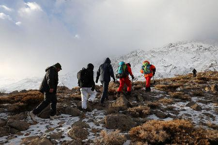 Members of emergency and rescue team search for the plane that crashed in a mountainous area of central Iran, February 19, 2018. REUTERS/Tasnim News Agency